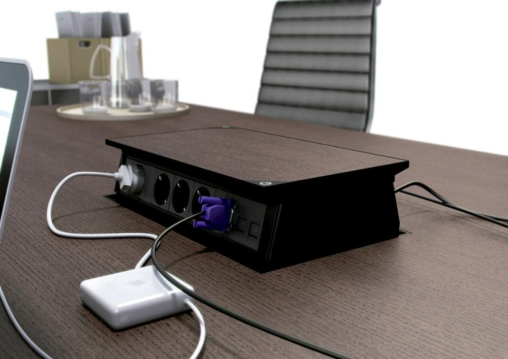 Boîtier de prises escamotable électriquement intégré dans une table de réunion