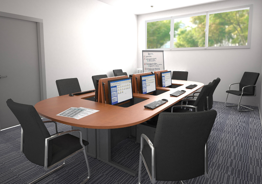 Salle de formation aménagée avec des meubles informatiques à écrans escamotables.