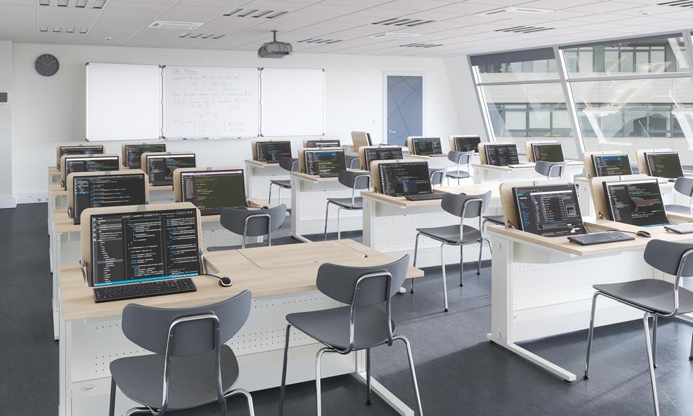 Salle de cours aménagée avec du mobilier à écrans escamotables